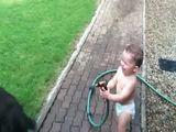 Kind duscht Hunde ab